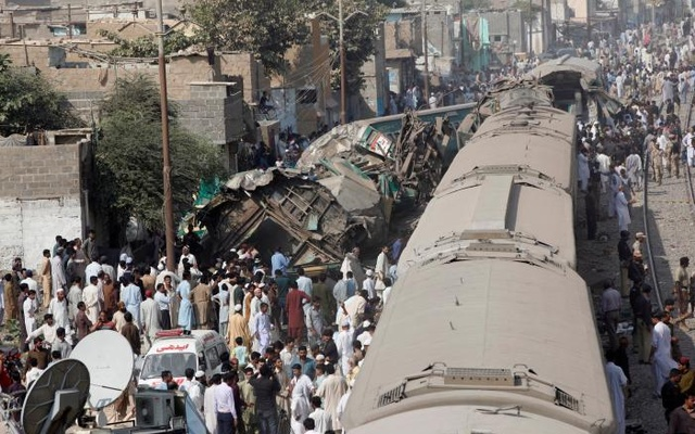 Spectators watch as rescue workers search a train which crashed in Karachi, Pakistan, November 3, 2016. Reuters