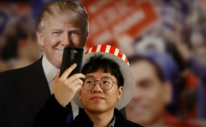 A man takes a selfie with a cut-out of Republican US presidential nominee Donald Trump during a US Election Watch event hosted by the US Embassy at a hotel in Seoul, South Korea, Nov 9, 2016. Reuters.