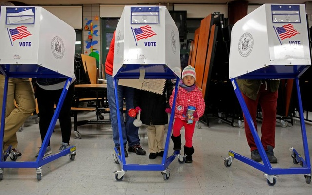 Myla Gibson, 3, waits as her father Ken Gibson fills out a ballot for the presidential election at the James Weldon Johnson school in the East Harlem neighbourhood of Manhattan, New York City. Reuters