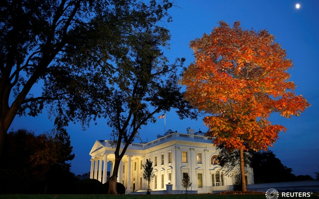 A tree is awash in autumn colour as the moon rises over the White House on election night in Washington. Reuters