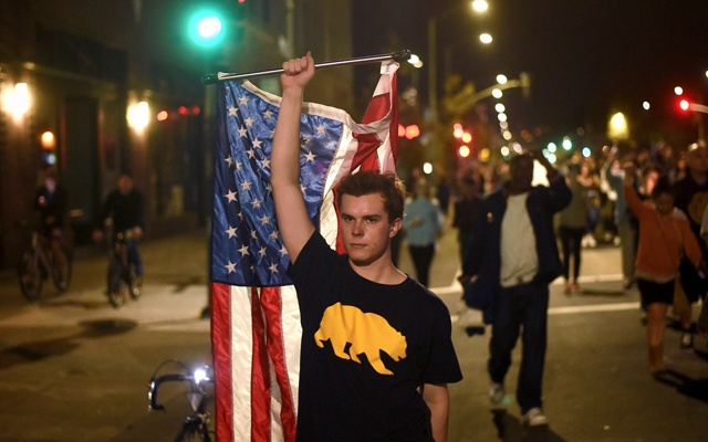 A young person waves an American flag during a anti-Trump demonstration in Oakland, California. Reuters