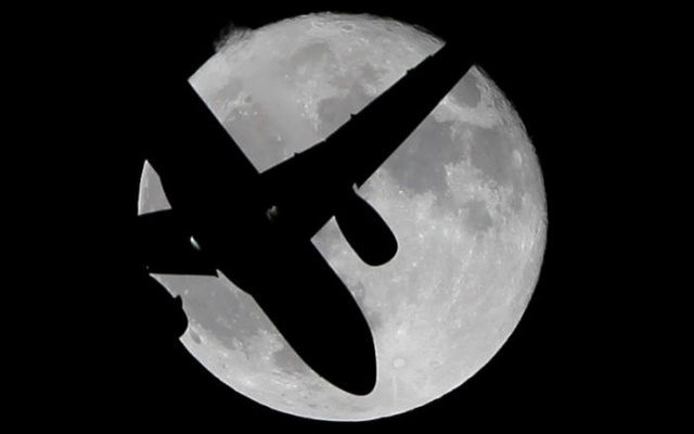 A passenger aircraft flies past a super moon in Ardales, southern Spain, Oct 17, 2016. Reuters