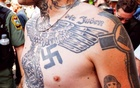A supporter of the Ku Klux Klan is seen with his tattoos during a rally at the statehouse in Columbia, South Carolina July 18, 2015. Reuters