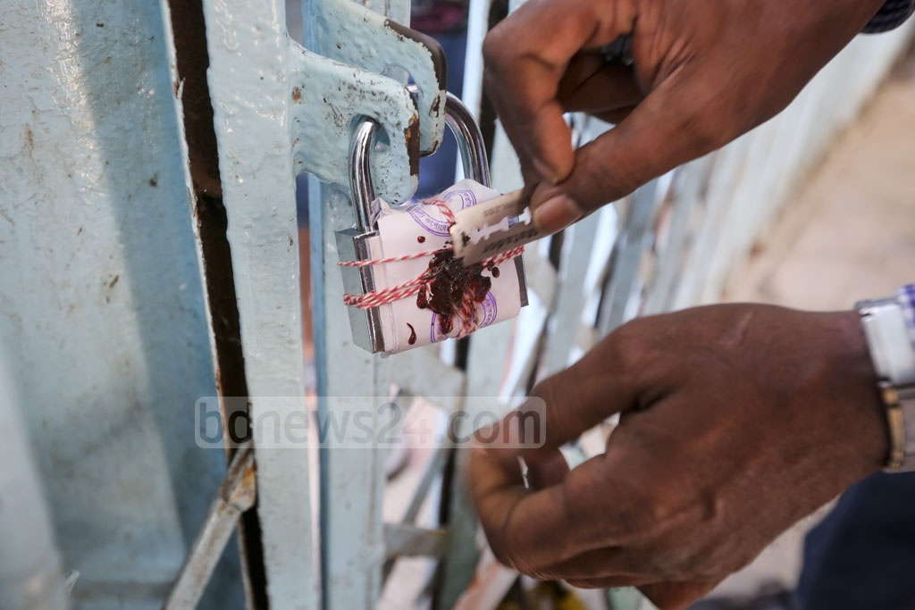 Officials locking down the entrance of 'Shishu Mela', a children's amusement park in Shyamoli, on Saturday for not paying lease rent for over a decade. Photo: asaduzzaman pramanik