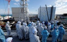 Members of the media, wearing protective suits and masks, receive briefing from Tokyo Electric Power Co (TEPCO) employees (in blue) in front of the No. 1 (L) and No. 2 reactor buildings at TEPCO's tsunami-crippled Fukushima Daiichi nuclear power plant in Okuma town. Reuters