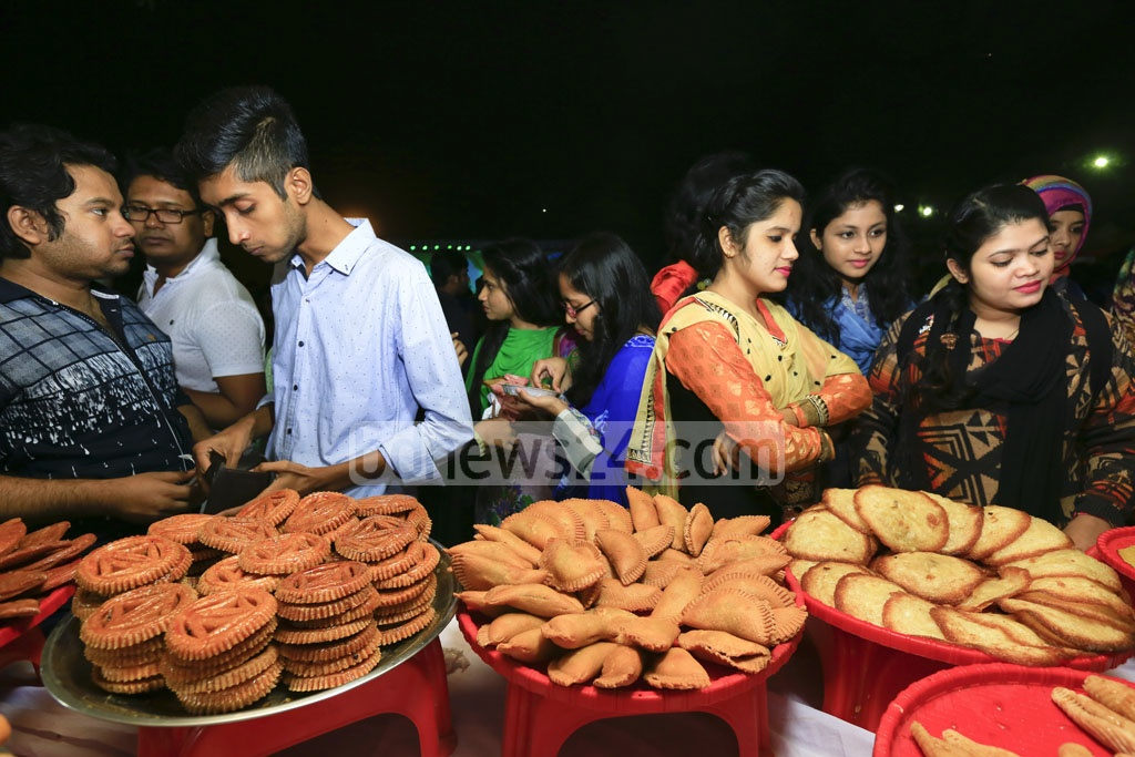 Visitors crowd round a traditional winter cake shop at 'Nabanna Utsab' or harvesting festival at Dhanmondi Rabindra Sarobar on Thursday. Photo: mostafigur rahman