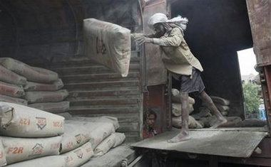 A labourer unloads cement sacks from the wagon of a train at a yard in Kolkata June 25, 2012. Reuters