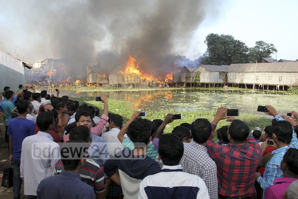 Onlookers gather at the other side of Gulshan Lake to see the fire that burnt hundreds of shanties in Karhail slum on Sunday.