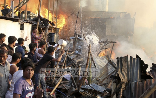 Locals joined hands with trained Fire Service men to douse the fire that burnt hundreds of shanties at Karhail Slum in Dhaka on Sunday.