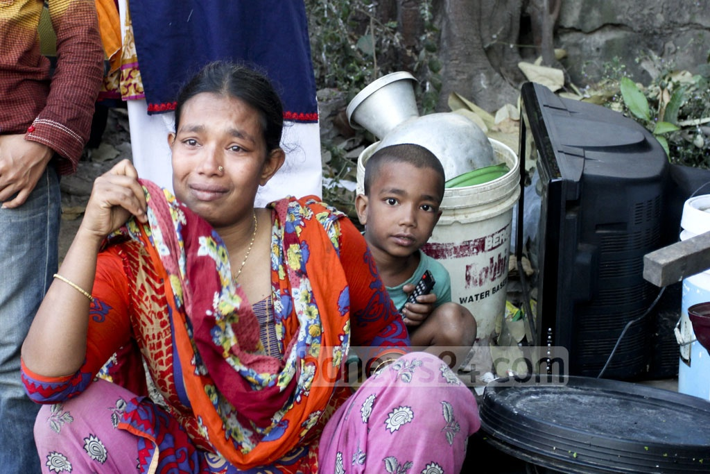 A family, managed to save some of their belongings, look with teary eyes at the flames that raged across Karhail slum at Mohakhali in the capital on Sunday. Over 500 thatched hoses gutted in fire.
