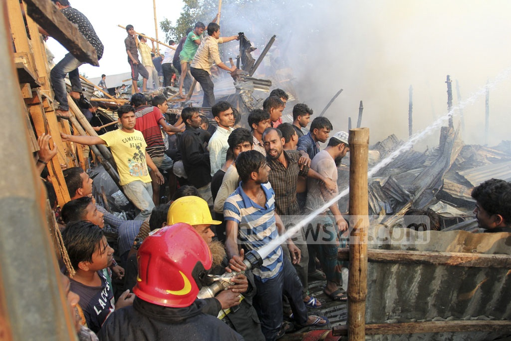 Fire Service personnel and some local volunteers trying to douse the flames at Karhail slum in Dhaka's Mohakhali on Sunday.
