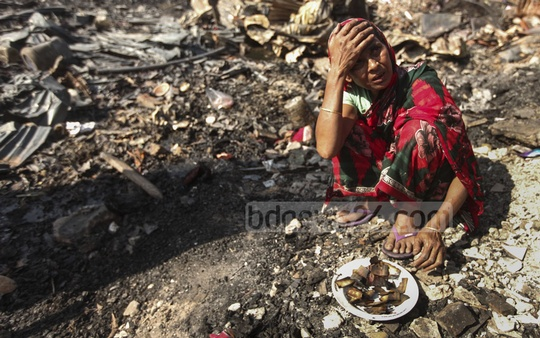 A woman sits surrounded by ruins from the fire at Korail slum. Photo taken on Monday.