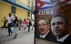Tourists pass by images of US President Barack Obama and Cuban President Raul Castro in a banner that reads 'Welcome to Cuba' at the entrance of a restaurant in downtown Havana, Mar 17, 2016. Reuters