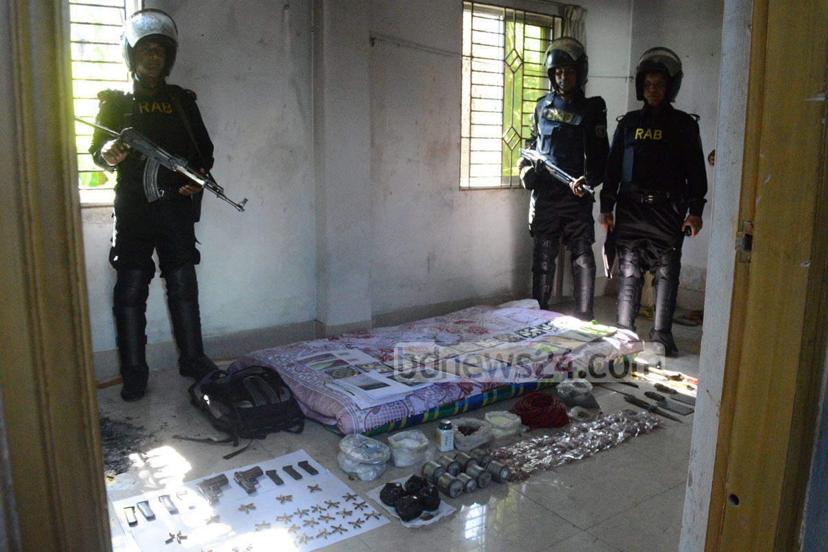 Law enforcers stand with siezed firearms, explosives and jihadi literature after a raid on suspected Harkat-ul-Jihad militant hideout in Chittagong's Colonel Haat on Thursday. Photo: suman babu