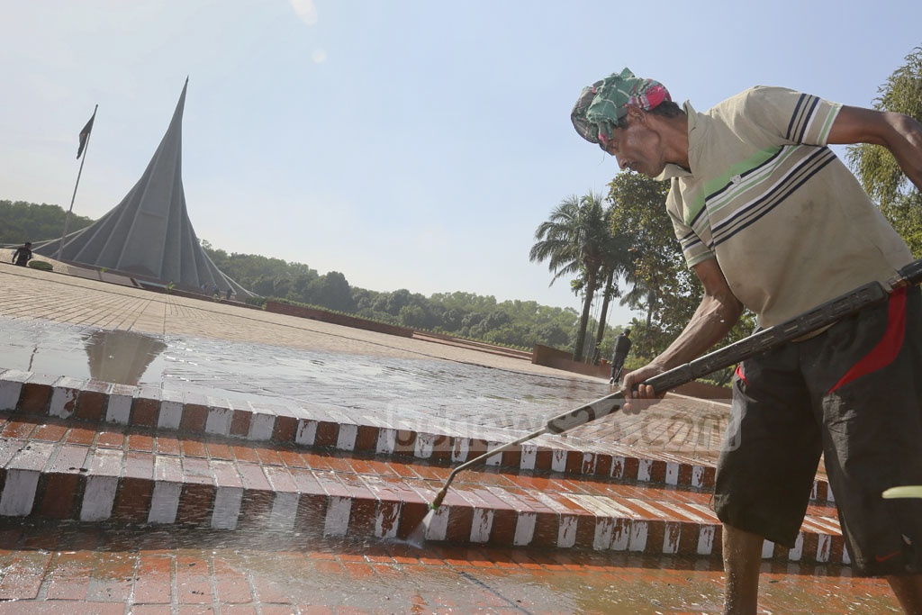 A worker cleans the National Memorial at Savar ahead of the Victory Day celebrations. Photo: asaduzzaman pramanik