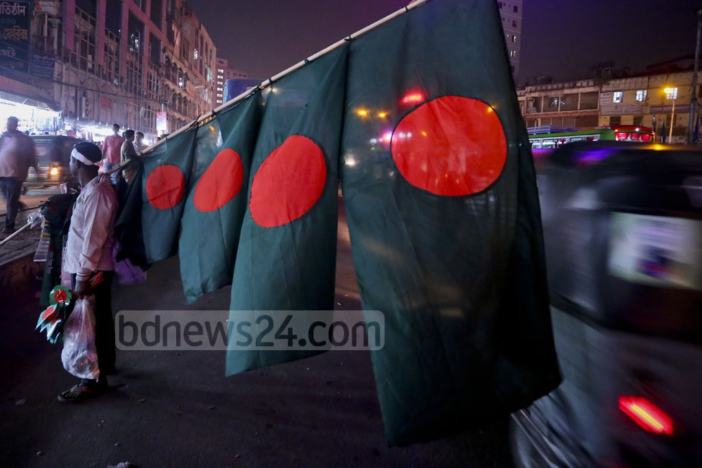 A man is selling national flags in the capital's Farmgate on Tuesday ahead of Victory Day. Photo: abdul mannan