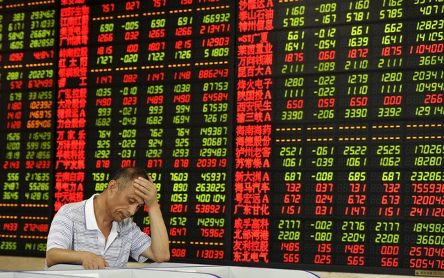 An investor looks at a computer screen in front of an electronic board showing stock information at a brokerage house in Fuyang, Anhui province, China, Aug 5, 2015. Reuters