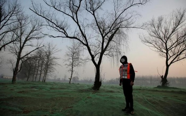Artist Liu Bolin wearing a vest with 24 mobile phones stands in smog as he live broadcasts air pollution in the city on the fourth day after a red alert was issued for heavy air pollution in Beijing, China, Dec 19, 2016. Reuters