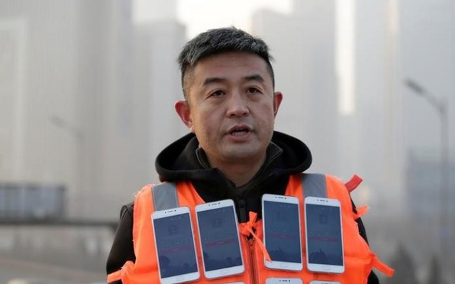 Artist Liu Bolin wearing a vest with 24 mobile phones speaks during a Reuters interview after a live broadcast of air pollution in the city on the fourth day after a red alert was issued for heavy air pollution in Beijing, China, Dec 19, 2016. Reuters