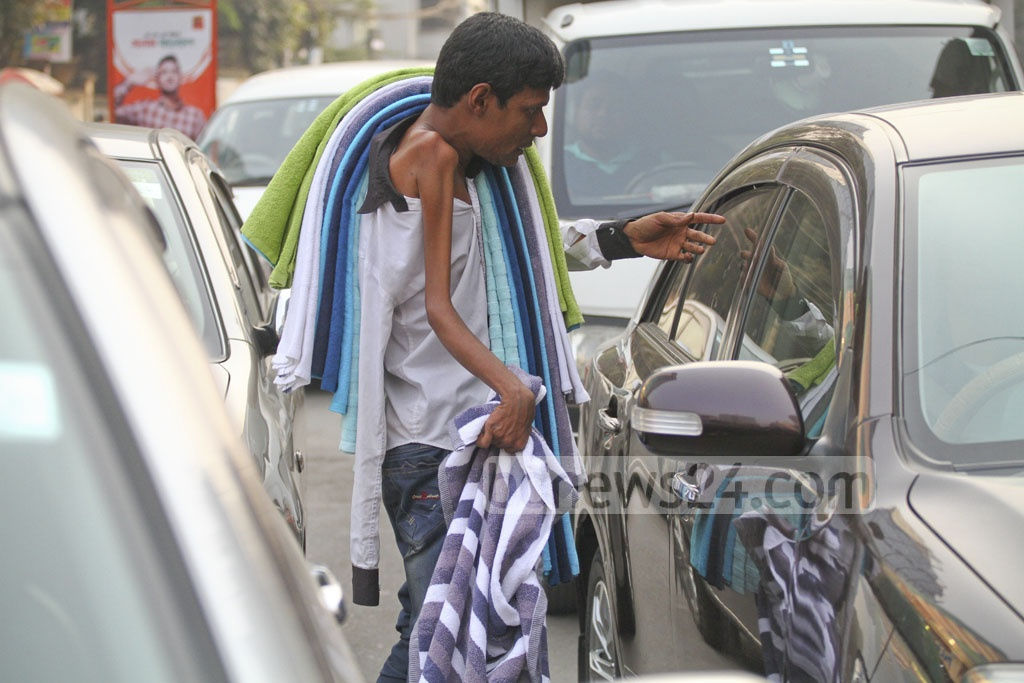 Physically-challenged Aminul Islam used to beg at the Dhaka City's traffic signals. Now he has changed career to sell towels. The father of two school-goers says he earns Tk 400-500 selling 10-15 towels a day. Photo: abdul mannan