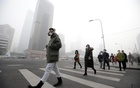 A man wearing a respiratory protection mask walks toward an office building during the smog after a red alert was issued for heavy air pollution in Beijing's central business district, China, Dec 21, 2016. Reuters
