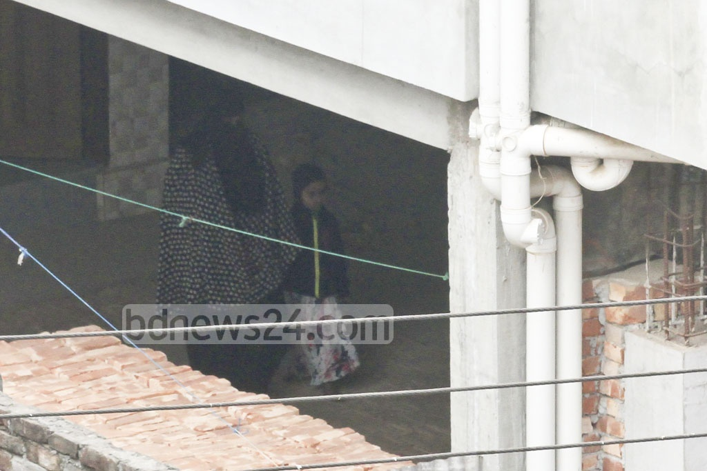 Militant Sumon's wife is seen coming out with militant Iqbal's 4-year-old daughter from the house raided by police in Dhaka's Ashkona on Saturday. She let the girl go, and seconds later, blew herself up using an improvised suicide vest. The child was taken to hospital with splinter injuries.