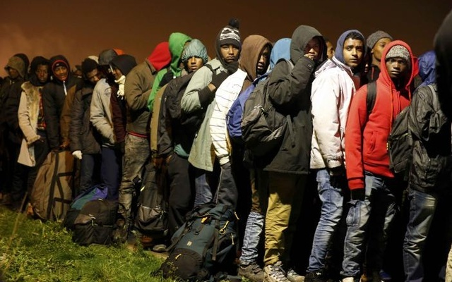 Migrants with their belongings queue as their evacuation and transfer to reception centres in France, and the dismantlement of the camp called the 'Jungle' in Calais, France, starts Oct 24, 2016. Reuters
