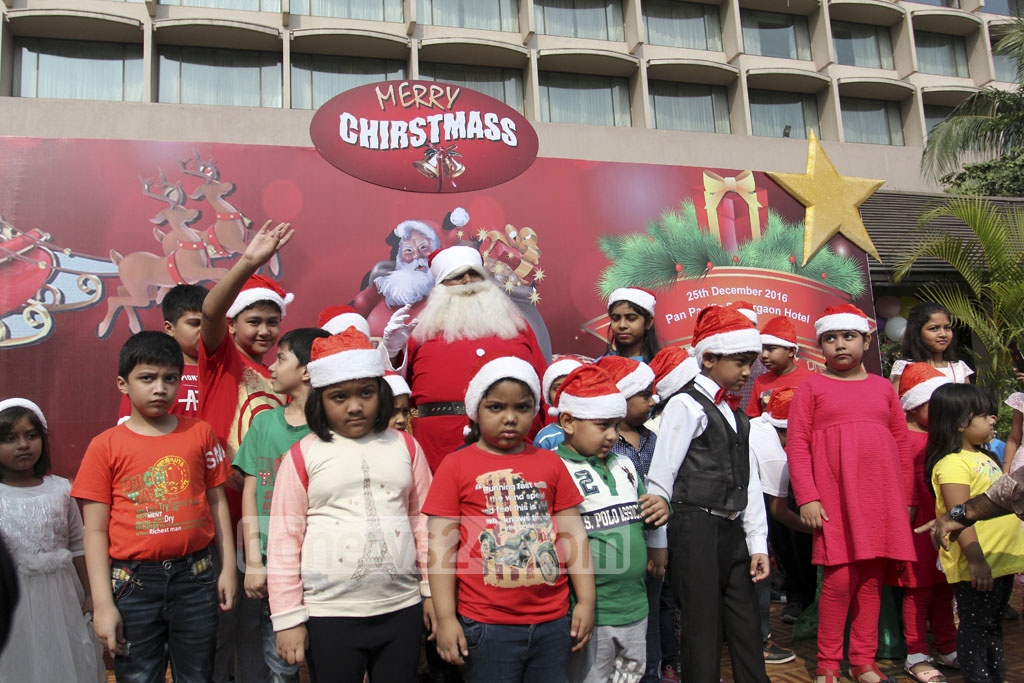 Santa Claus giving presents at a five-star hotel in Dhaka on Sunday during Christmas celebrations. Photo: asif mahmud ove