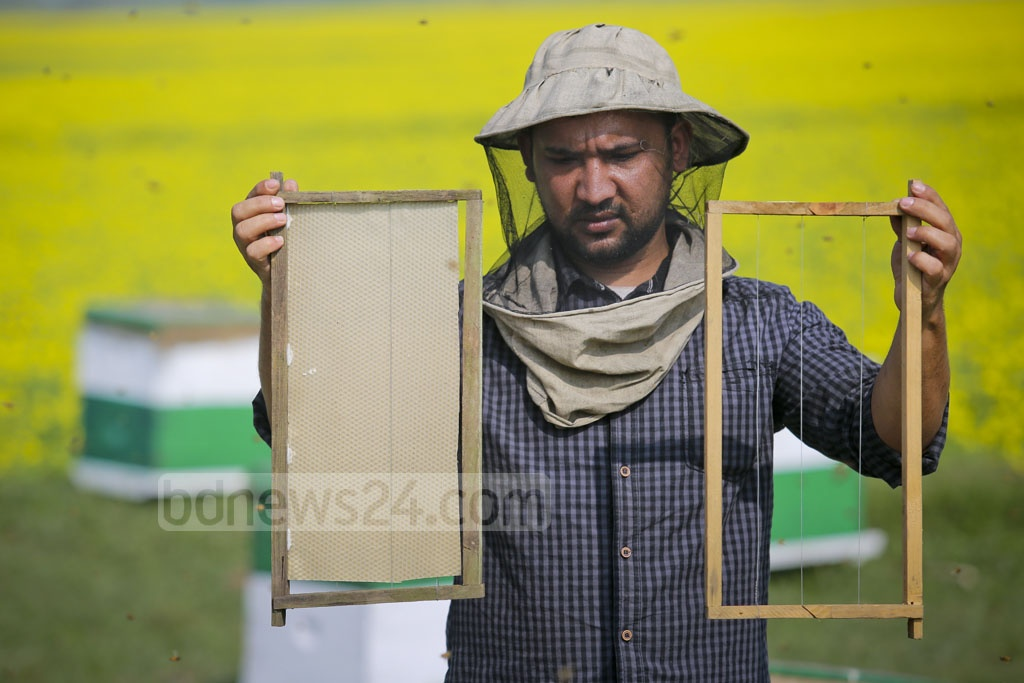 A sheet made of beeswax is attached to a wooden frame before they are put inside the hive. Photo: asaduzzaman pramanik