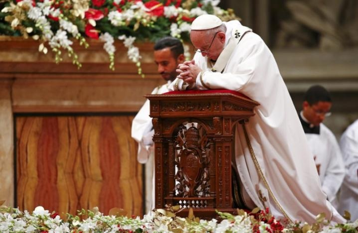 Pope Francis kneels as he leads the Christmas night Mass in Saint Peter's Basilica at the Vatican December 24, 2016. REUTERS