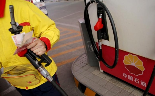 A gas station attendant pumps fuel into a customer's car at PetroChina's petrol station in Beijing, China, March 21, 2016. Reuters