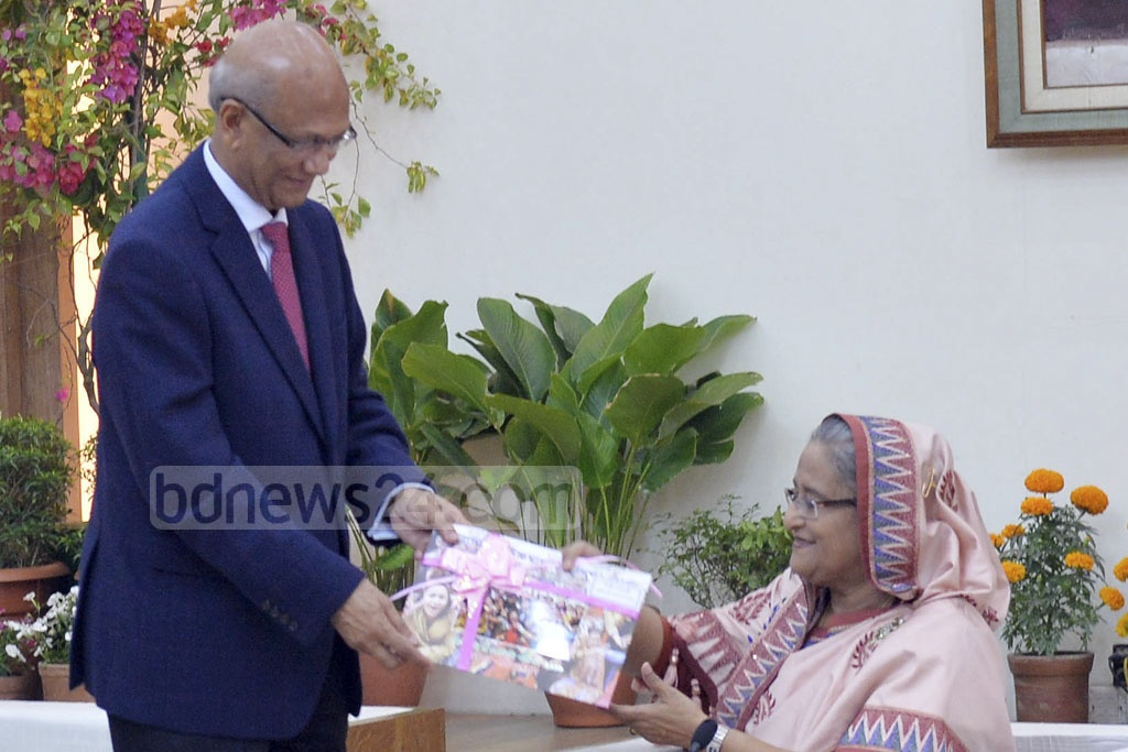 Education Minister Nurul Islam Nahid presents Prime Minister Sheikh Hasina with a report on the Junior School Certificat (JSC) and Junior Dakhal Examinations (JDC) at the Ganabhaban on Thursday. Photo: PID