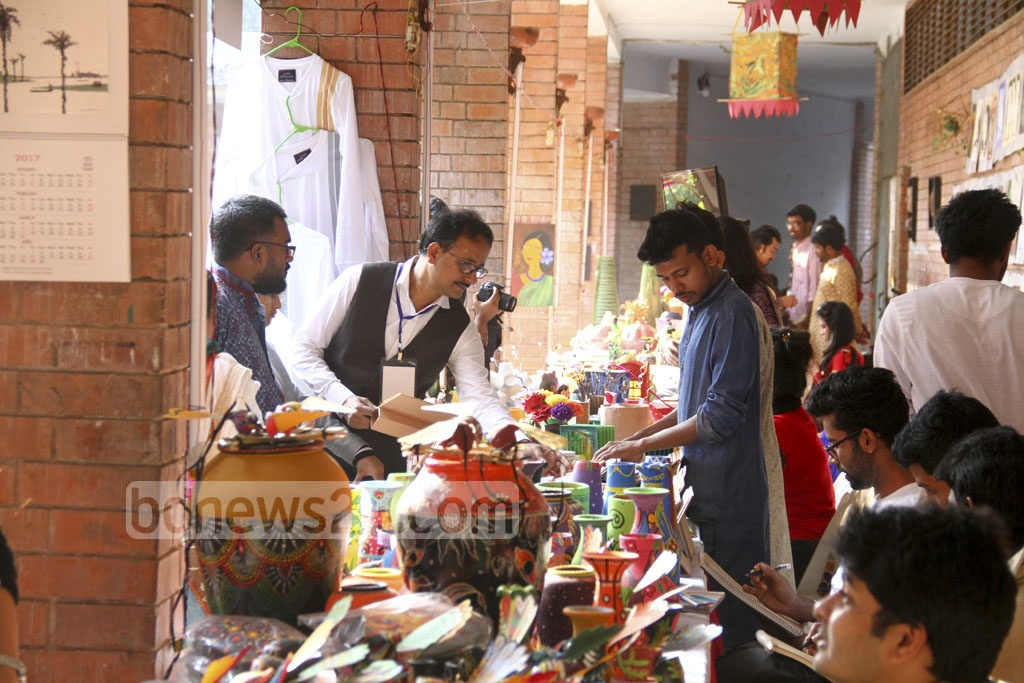 Visitors are looking around stalls set up by the student of the Faculty of Fine Arts in Dhaka University on the occasion of 102nd birth anniversary of Shilpacharya Zainul Abedin on Friday. Photo: abdul mannan