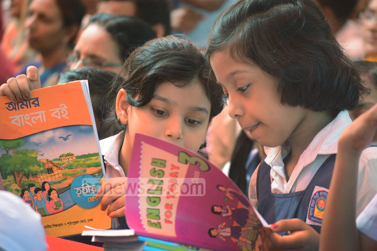 Students look over their new text books after a long wait at the Textbook Festival on Sunday. Photo: suman babu