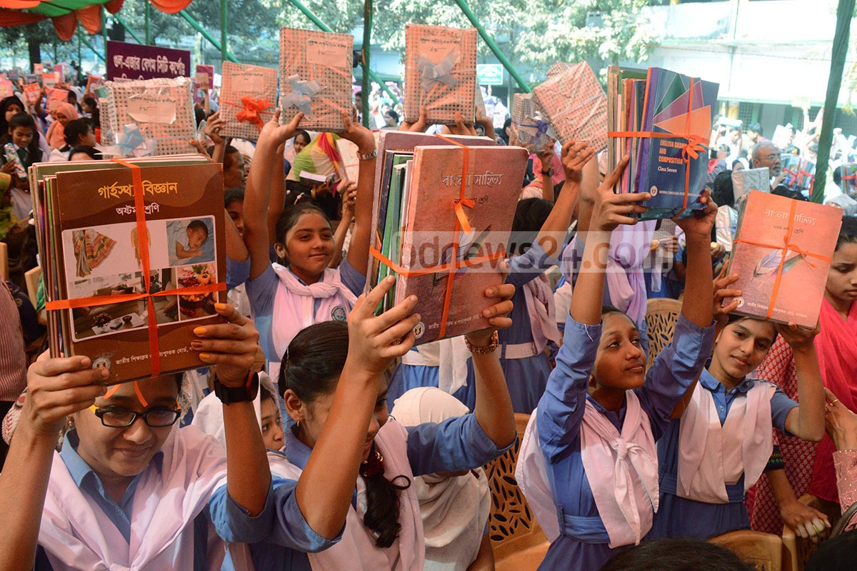 Schoolchildren raise their new textbooks in the air at the Textbook Festival on Sunday. Photo: suman babu