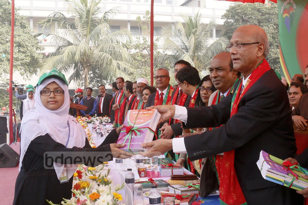 Education Minister Nurul Islam Nahid distributing textbooks among students at Azimpur Government Girls' School and College in Dhaka during the Textbook Festival on Sunday. Photo: asif mahmud ove