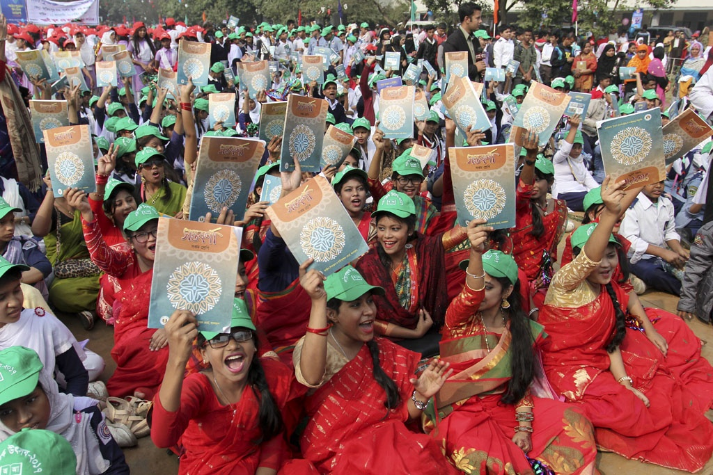 Schoolchildren raise their new textbooks in the air at the Textbook Festival on Sunday. Photo: asif mahmud ove