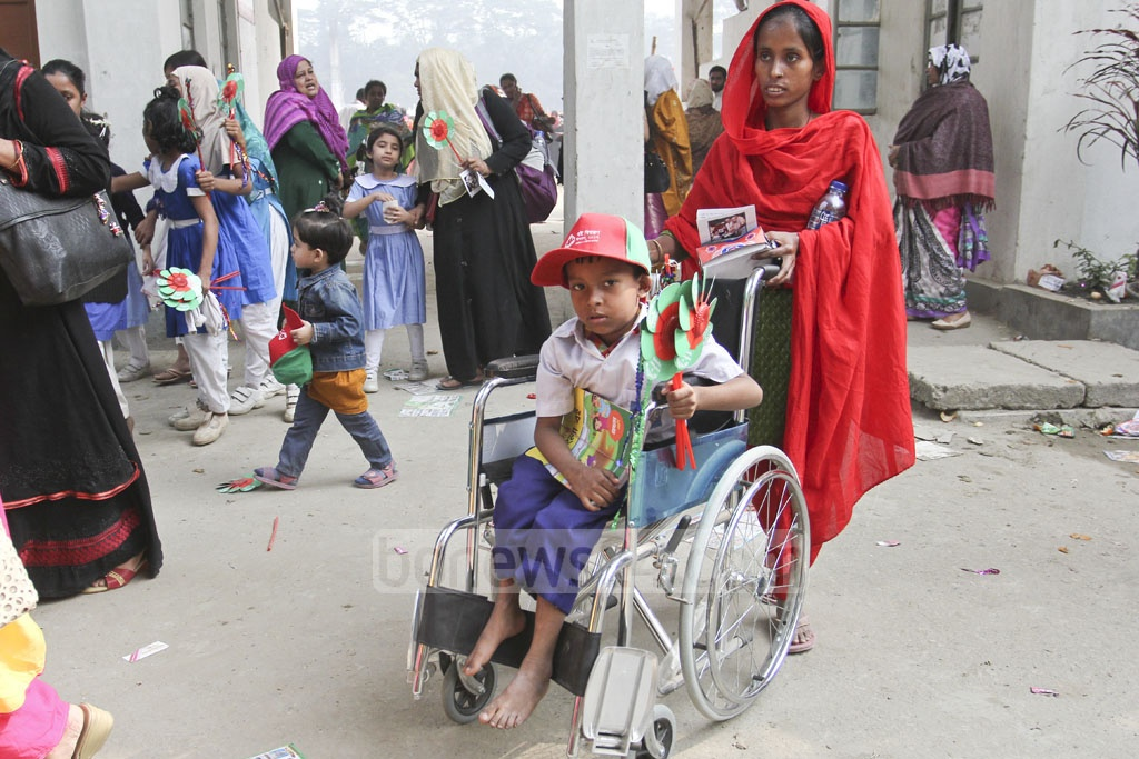 Yasin, a wheelchair-bound student in first standard at West Bhashantek Government Primary School, attends the Textbook Festival at the Dhaka University play ground on Sunday. Photo: asif mahmud ove