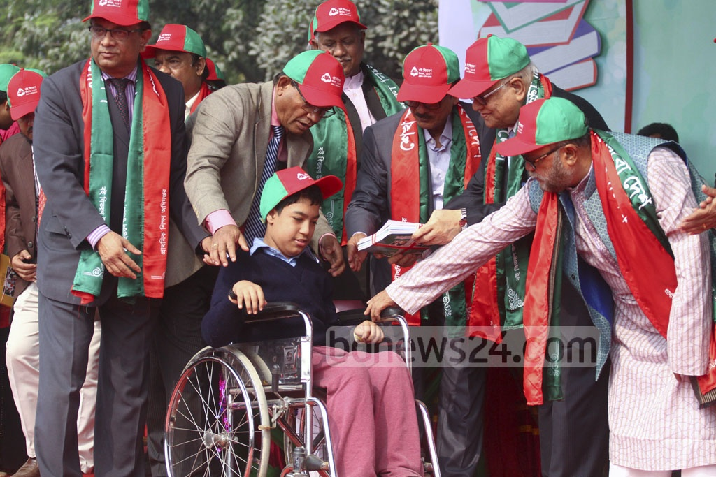 Primary and Mass Education Minister Mostafizur Rahman and Finance Minister AMA Muhith distribute textbooks to students on the Dhaka University play ground during the Textbook Festival on Sunday. Photo: abdul mannan