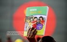 A schoolboy raises his new textbooks in the air at the Textbook Festival on Sunday. Photo: abdul mannan