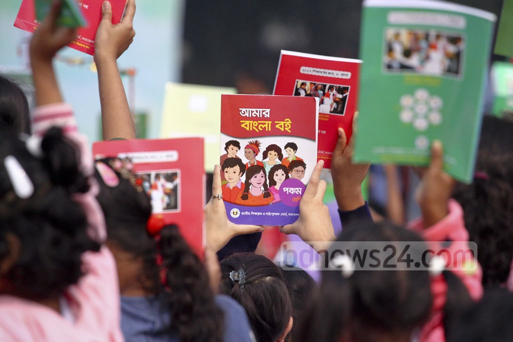 Schoolchildren raise their new textbooks in the air at the Textbook Festival on Sunday. Photo: abdul mannan