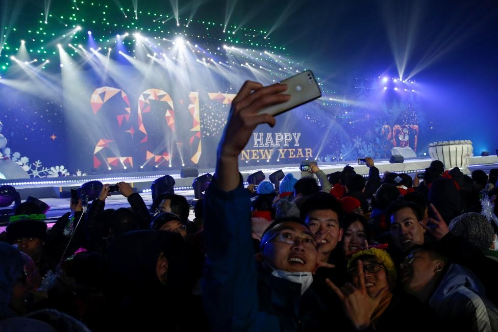 People pose for pictures as they attend a New Year's Eve countdown event in Beijing, China, December 31, 2016. REUTERS