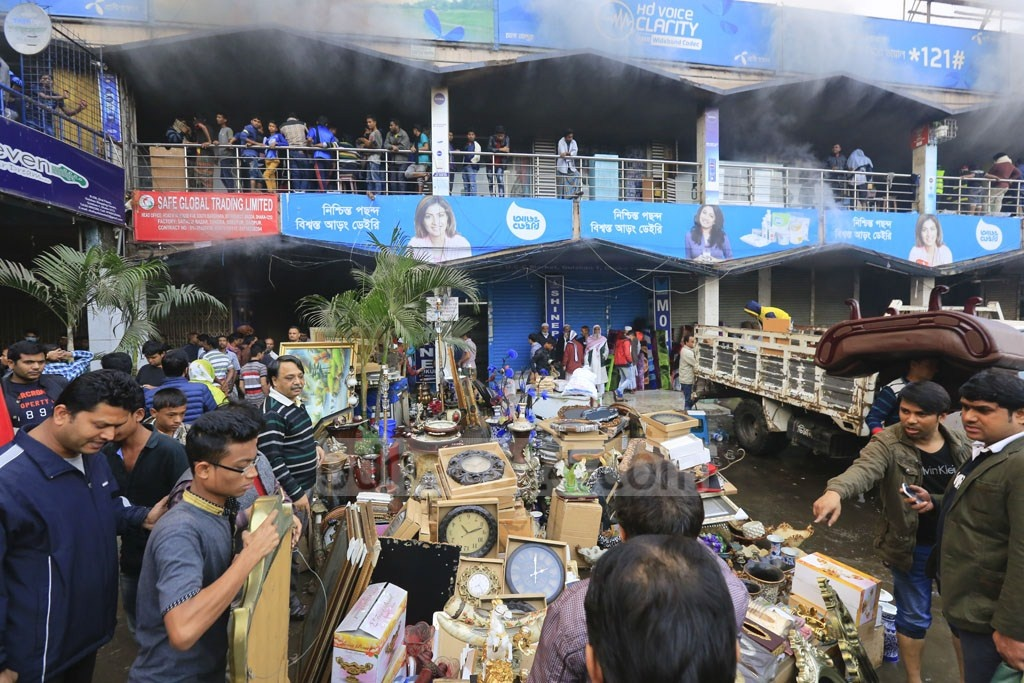 Goods from shops at Gulshan DNCC market piled up outside the building that caught fire on Tuesday. Photo: mostafigur rahman