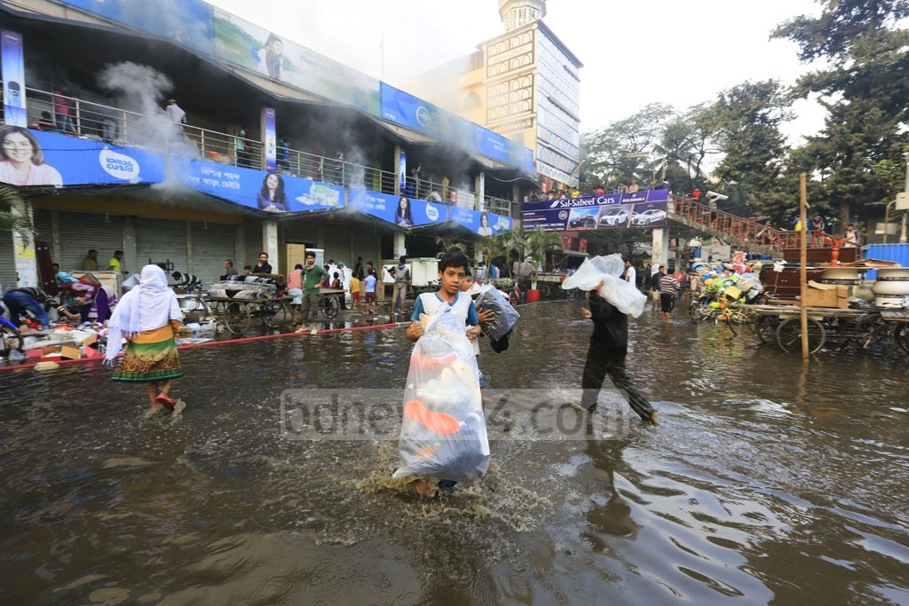 Water used to douse flames spills into the parking area of the Gulshan DNCC market on Tuesday. Photo: mostafigur rahman