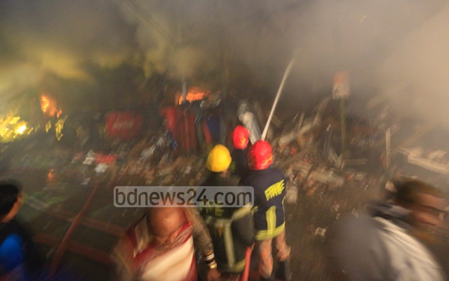 Fire crew frantically try to douse the fire ravaging DCC Market in the capital's Gulshan-1 on Tuesday. bdnews24.com Chief News Photographer Mostafigur Rahman clicked the photo at 4:30am.