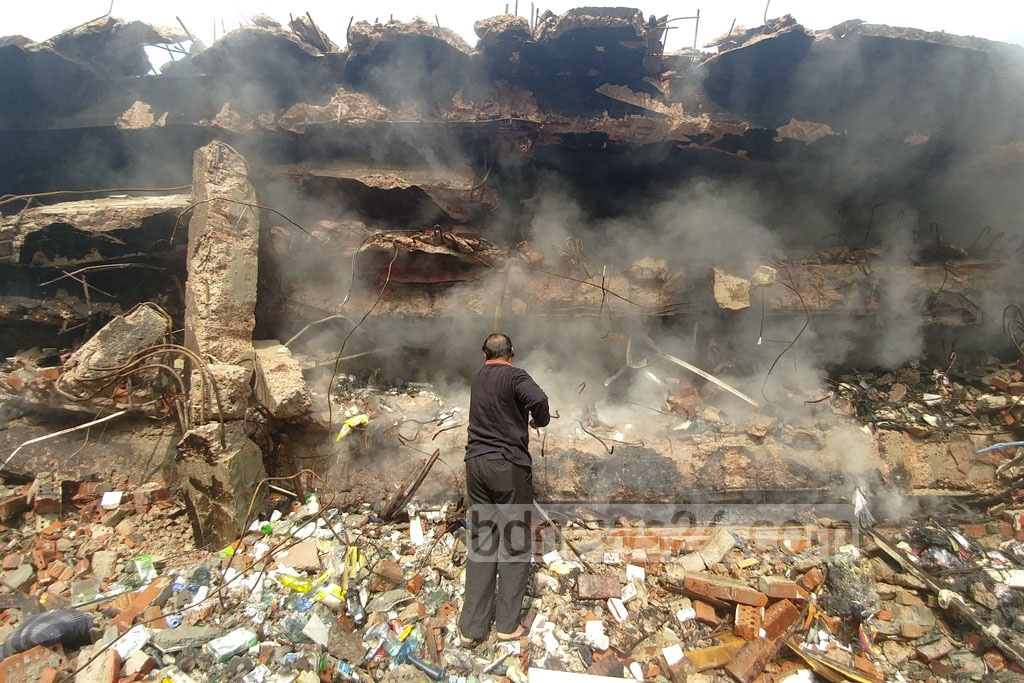 A shop employee searches for items that may have survived the massive fire at Gulshan DNCC Market. Photo: abdul mannan