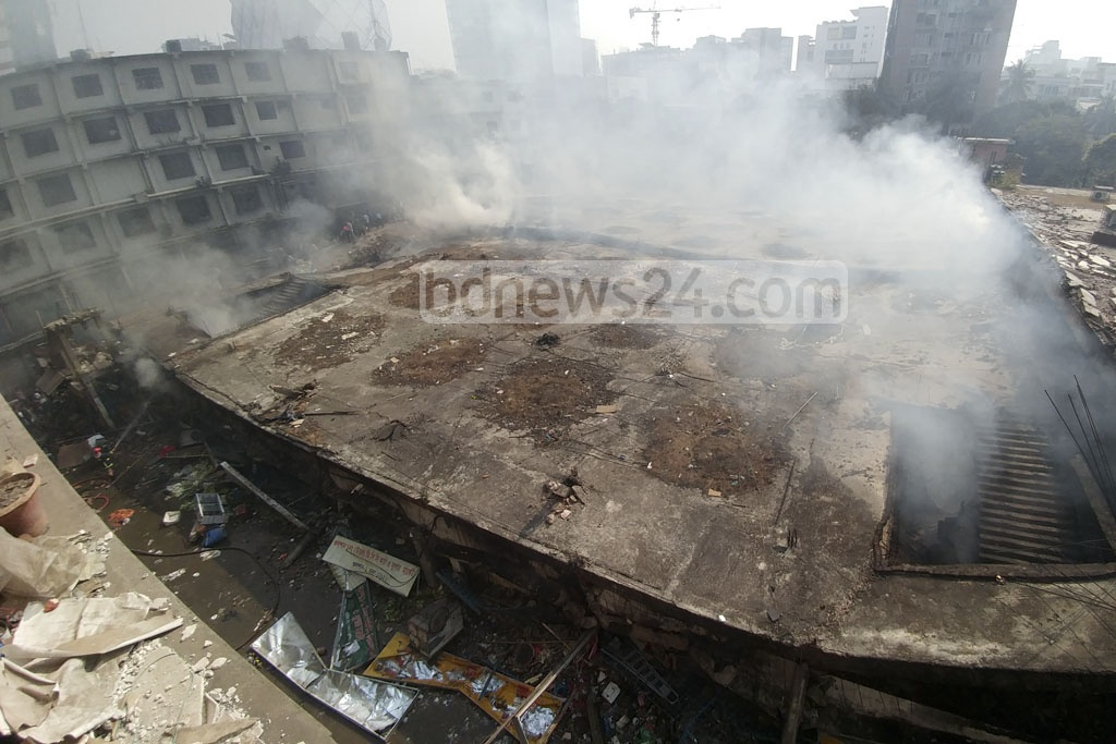 Smoke is seen coming out of the ruins of Gulshan DNCC Market on Wednesday after it took more than a day to put out the massive fire. Photo: abdul mannan
