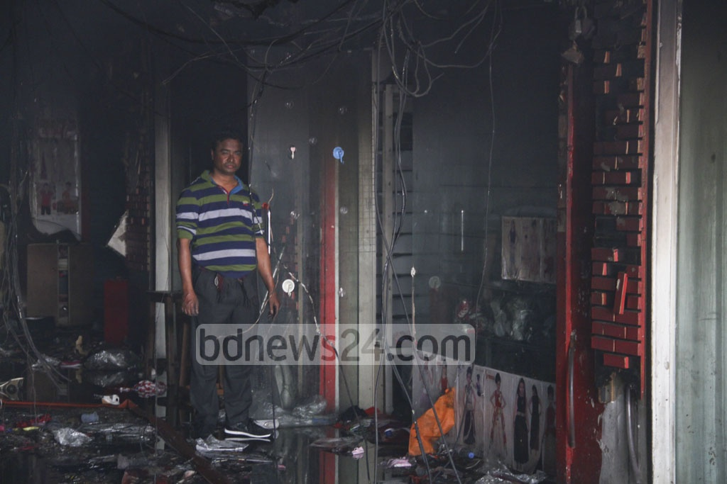 A businessman stands in front of his shop destroyed by the massive fire at Gulshan DNCC Market. Photo: abdul mannan