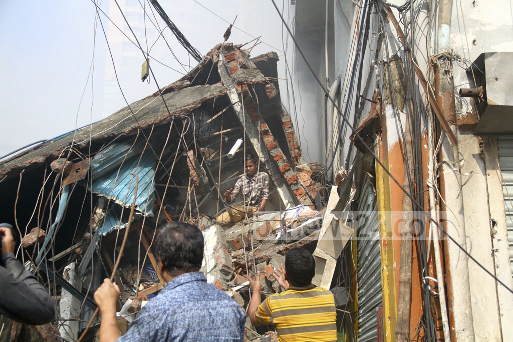 A child worker risks his life to retrieve shop items by climbing on debris after the massive fire at Gulshan DNCC Market. Photo: abdul mannan