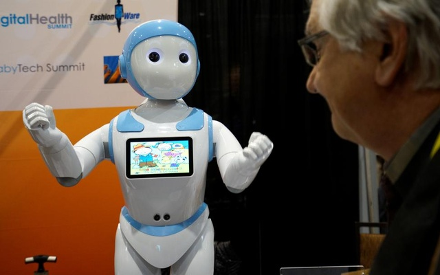 A showgoer looks at the Avatar iPal robot for childen, eldercare and retail applications. Reuters